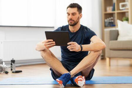 自宅でエクササイズマットにタブレットコンピュータを持つ男