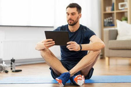 man with tablet computer on exercise mat at home