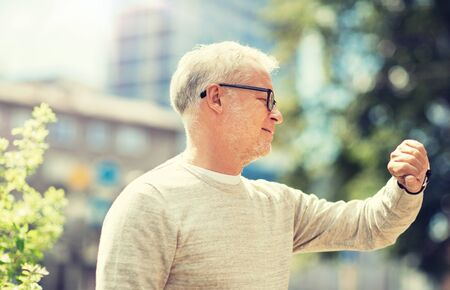 senior man checking time on his wristwatch Фото со стока