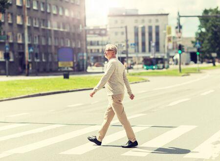 homme aîné marchant le long du passage pour piétons de la ville