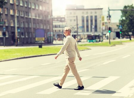 senior man walking along city crosswalk