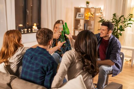 friends clinking drinks at home in evening Imagens