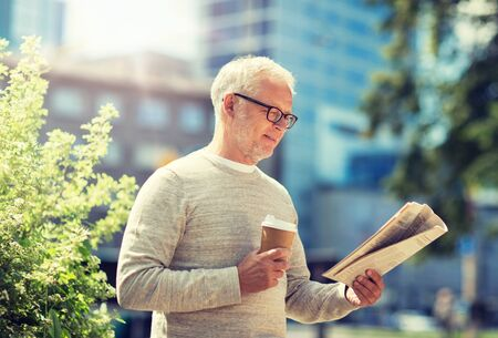 senior man reading newspaper and drinking coffee