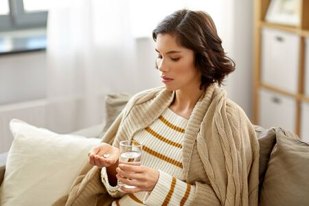 sick woman taking medicine with water at home
