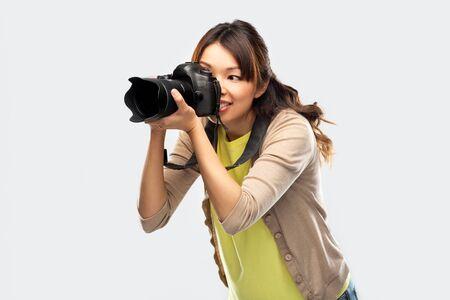 Fotógrafa asiática con cámara digital