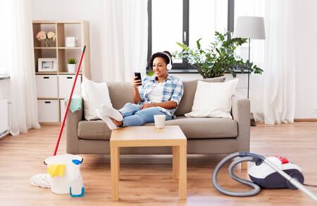 woman in headphones resting after home cleaning Stock Photo