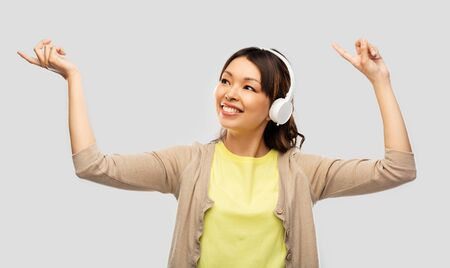 asian woman in headphones listening to music