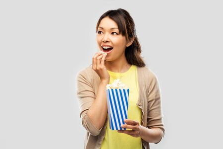 smiling asian woman eating popcorn
