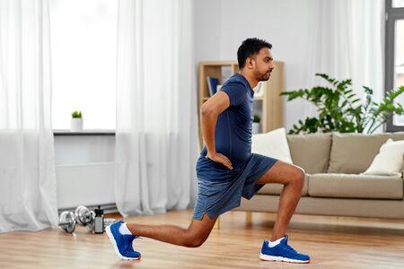Hombre indio haciendo ejercicio y estocada en casa Foto de archivo