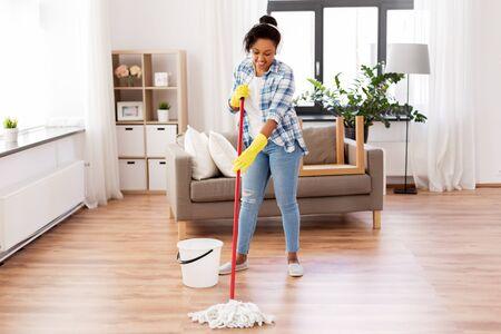 mujer africana, o, ama de casa, limpieza, piso, en casa