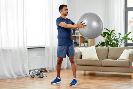 indian man exercising with fitness ball at home Stock Photo