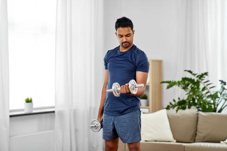 Hombre indio haciendo ejercicio con pesas en casa Foto de archivo