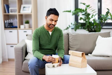 indian man with takeaway coffee and food at home Stock Photo