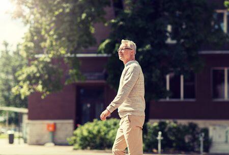 senior man walking along summer city street