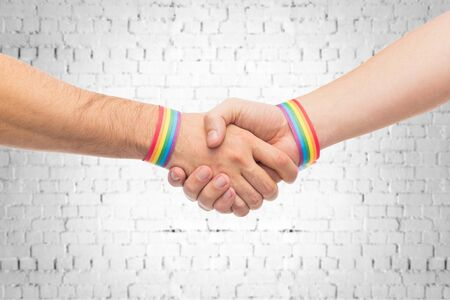 hands with gay pride wristbands make handshake 写真素材
