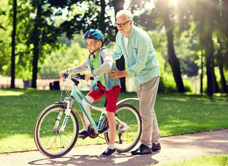 grandfather and boy with bicycle at summer park 스톡 콘텐츠
