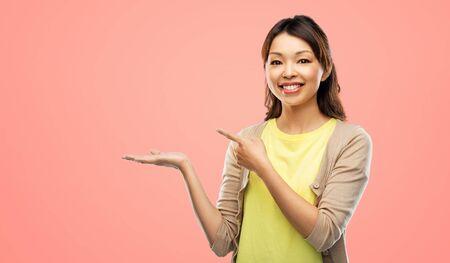femme asiatique heureuse tenant quelque chose à portée de main