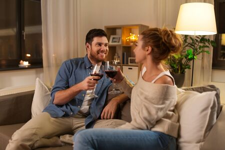 happy couple drinking red wine at home in evening