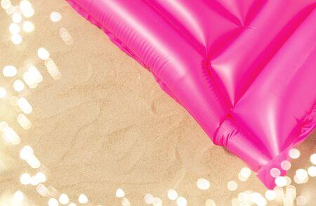 pink swimming mattress on beach