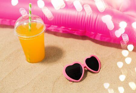 sunglasses, juice and pool mattress on beach sand