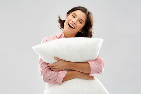 happy young woman in pajama hugging pillow Stok Fotoğraf