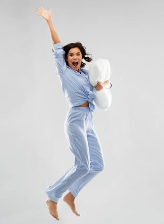 happy woman in blue pajama jumping with pillow