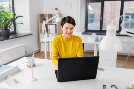 happy businesswoman with laptop working at office Standard-Bild - 124797856