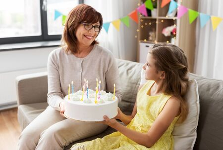 grandmother and granddaughter with birthday cake 스톡 콘텐츠