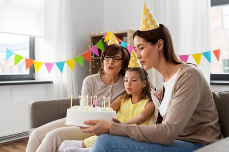 mother, daughter, grandmother with birthday cake