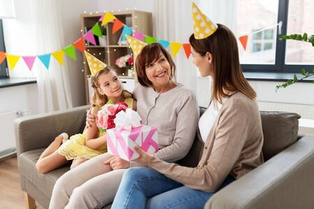 mother with gift greeting grandmother on birthday Stock Photo