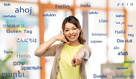 woman making phone call gesture over foreign words Stockfoto