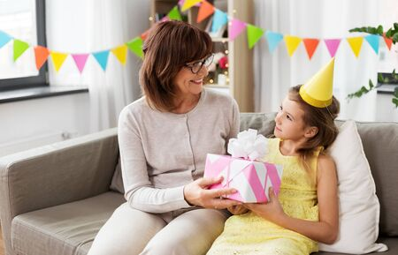 grandmother giving granddaughter birthday gift Stock Photo