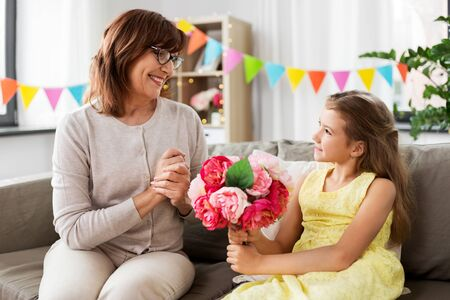 granddaughter giving grandmother flowers at home 스톡 콘텐츠