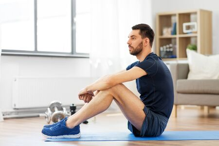 man resting on exercise mat at home Stock Photo