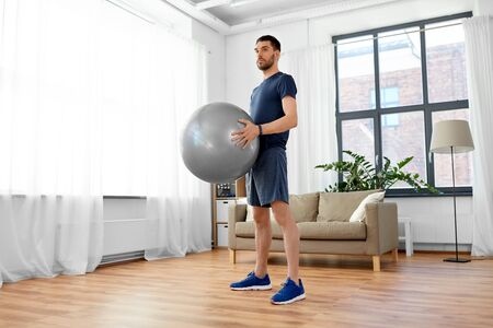man exercising with fitness ball at home