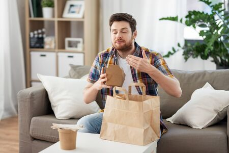 smiling man unpacking takeaway food at home Imagens
