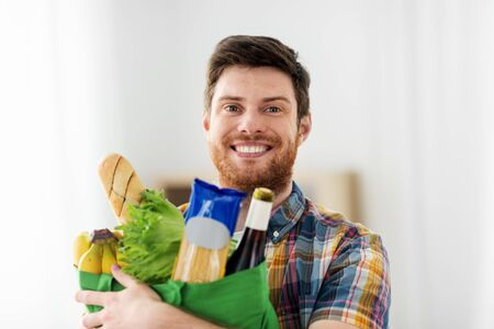 smiling young man with food in bag Stock Photo