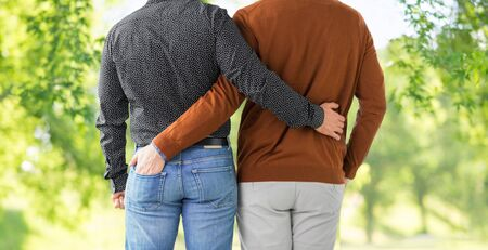 lgbt, same-sex relationships and homosexual concept - close up of hugging male gay couple over green natural background