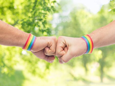 lgbt, same-sex love and homosexual relationships concept - close up of male couple hands with gay pride rainbow awareness wristbands making fist bump gesture over green natural background