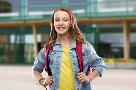 education and people concept - happy smiling teenage student girl with bag over school yard background