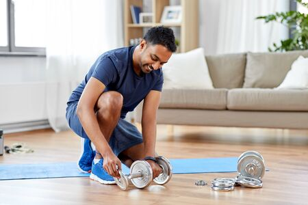 fitness, sport, weightlifting and bodybuilding concept - smilingindian man assembling dumbbells at home Banco de Imagens