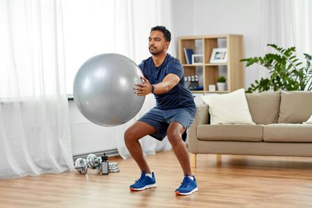 fitness, sport and healthy lifestyle concept - indian man exercising and doing squats with ball at home Stockfoto