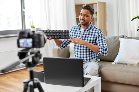 blogging, videoblog and people concept - indian male blogger with camera recording video review of computer keyboard and making so-so gesture at home Banco de Imagens
