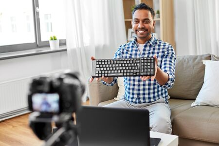 blogging, videoblog and people concept - indian male blogger with camera recording video review of computer keyboard at home