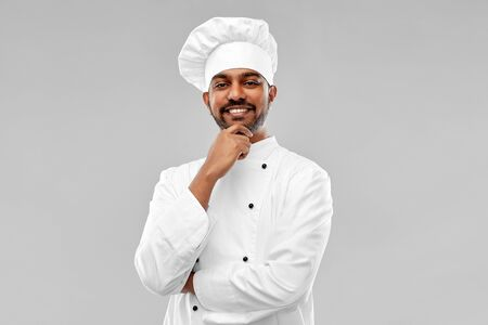 happy male indian chef in toque Stockfoto