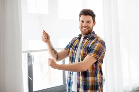 people concept - young man opening or closing roller blind on window at home Imagens