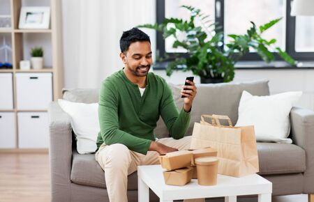 technology, consumption and people concept - smiling indian man using smartphone for food delivery at home Stockfoto