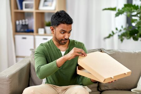 food delivery, consumption and people concept - excited indian man looking inside of takeaway pizza box at home