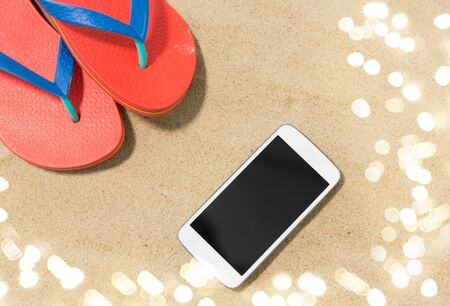 smartphone and flip flops on beach sand
