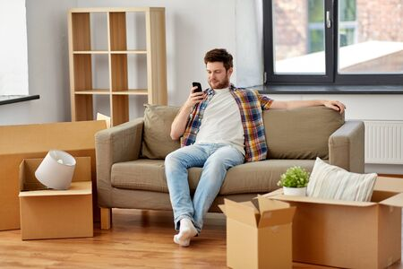 moving, people and real estate concept - happy man with smartphone and boxes sitting on sofa at new home Stockfoto